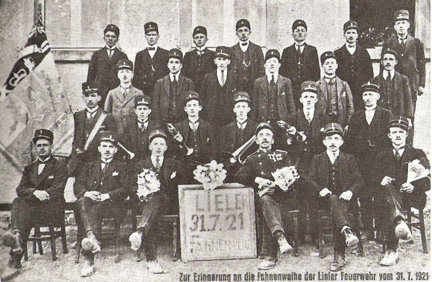 """Erinnerungsfoto von 1921 mit den ersten 4 """"Clairoen"""" und der ersten Fahne, die von 1933-1951 in Diensten der Musikgesellschaft stand. Der damalige Fahnenträger Blasen Michel rettete die Fahne vor der deutschen Besatzung."""